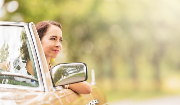 Vrouw zitten in een cabriolet auto glimlachend tijdens het rijden op een warme zomerdag.