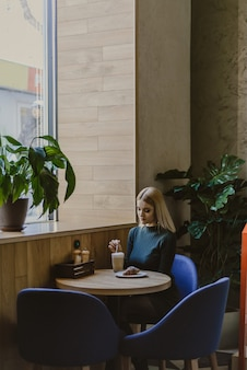 Vrouw zitten in een café in de ochtend met koffie en een croissant