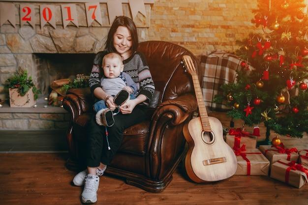 Vrouw zitten in een leunstoel met haar baby en een gitaar, een kerstboom en een schoorsteen achtergrond