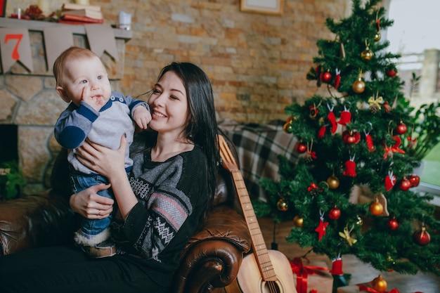 Vrouw zitten in een leunstoel met haar baby en een gitaar ernaast