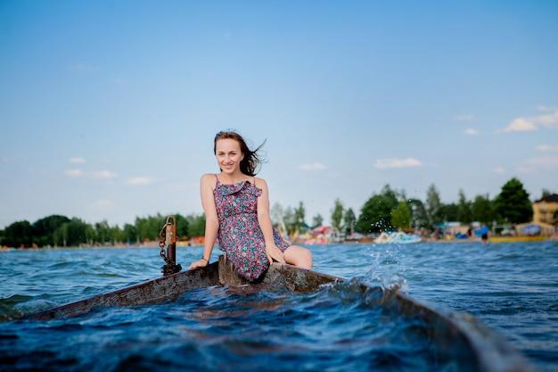 Vrouw zitten in een oude houten boot op een groot meer svityaz. concept van de zomer