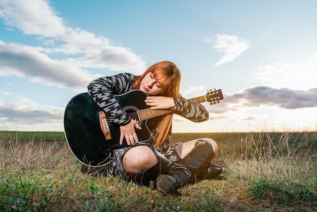 Vrouw zitten in een park haar zwarte gitaar knuffelen onder bewolkte hemel. concept liefde voor muziek