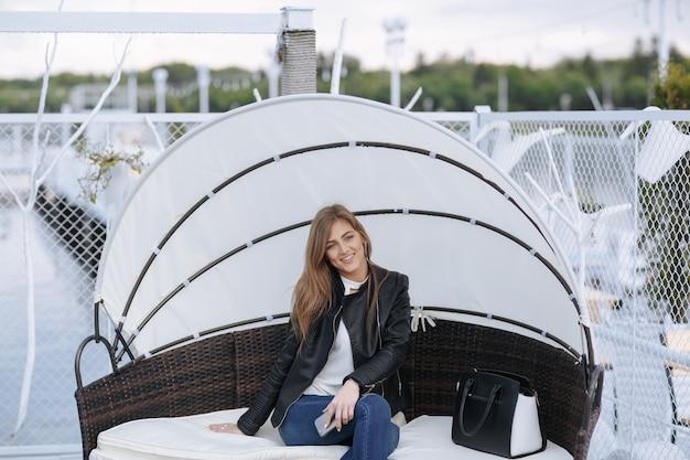 Vrouw zitten in een rieten stoel met het glimlachen paraplu