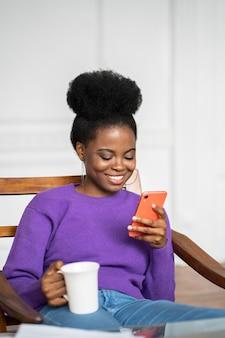 Vrouw zitten in een stoel, met behulp van mobiele slimme telefoon, chatten op sociale netwerken, thee of koffie drinken