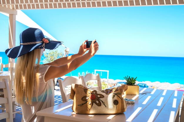 Vrouw zitten in een strandbar-restaurant en het nemen van selfie