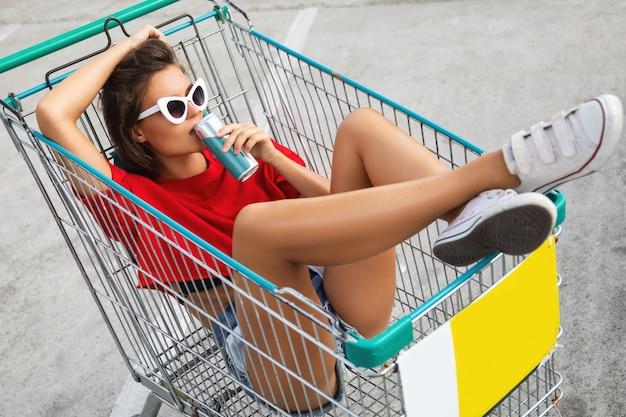Vrouw zitten in een winkelwagentje met frisdrank op het parkeren van de supermarkt