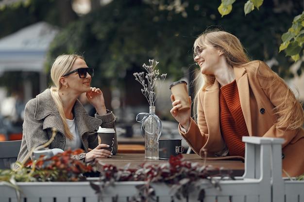Vrouw zitten in een zomerstad en koffie drinken