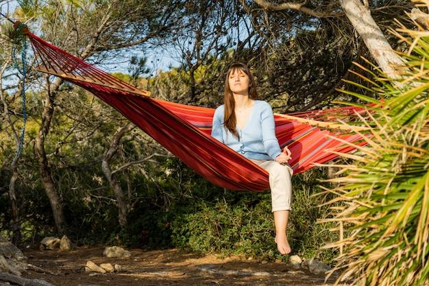 Vrouw zitten in hangmat mediteren met zon op gezicht in dennenbos