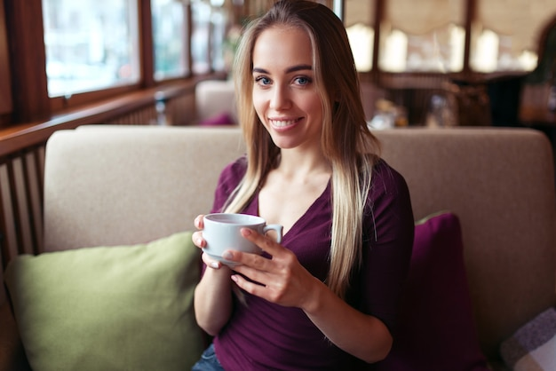 Vrouw zitten in het café met een kopje drank