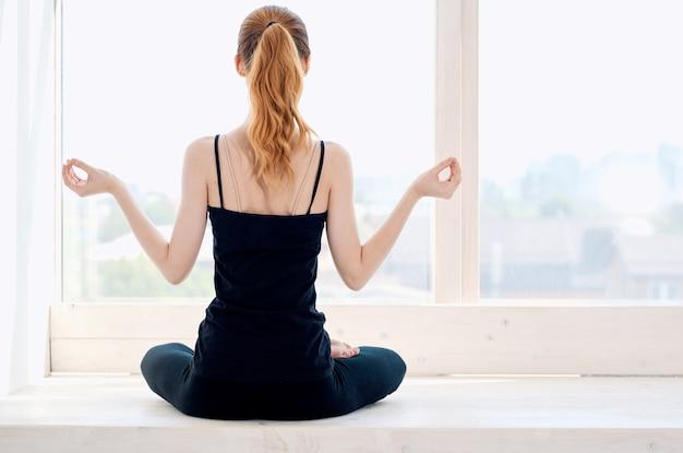 Vrouw zitten in lotushouding oefening meditatie yoga in de buurt van raam