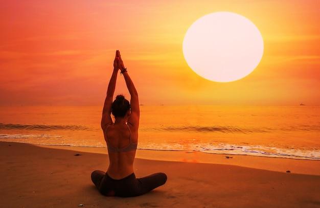 Vrouw zitten op een strand met armen gestrekt