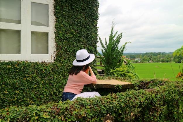 Vrouw zitten op het terras van boom bladeren bedekt landhuis, kijkend naar het rijstveld