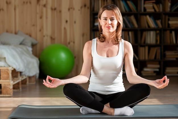 Vrouw zitten op yoga mat
