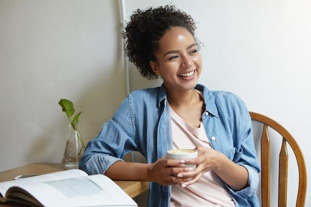 Vrouw zittend aan een tafel met een boek