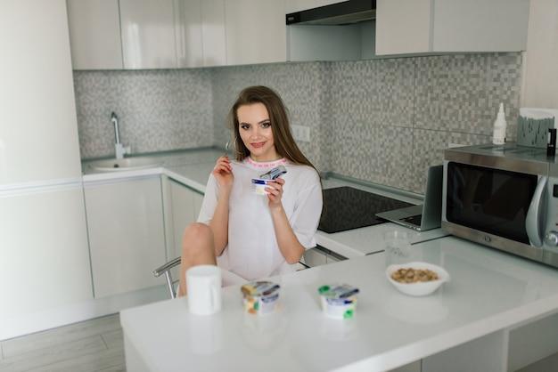 Vrouw zittend aan tafel in de keuken met een kopje koffie en een notitieblok