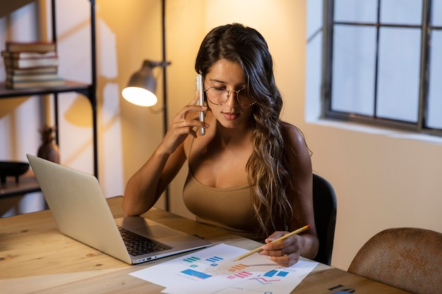 Vrouw zittend aan tafel praten over de telefoon en kijken naar papieren