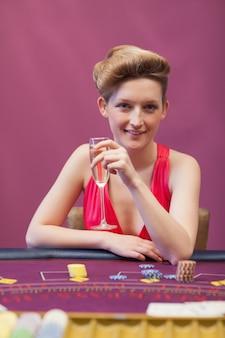Vrouw zittend aan tafel terwijl een glas champagne