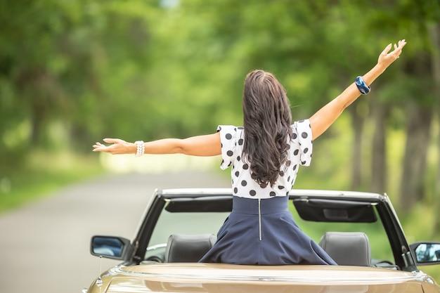 Vrouw zittend bovenop cabriolet met open armen gefotografeerd vanaf de achterkant.