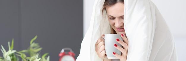Vrouw zittend in bed onder dekens en het drinken van thee ontbijt op bed concept