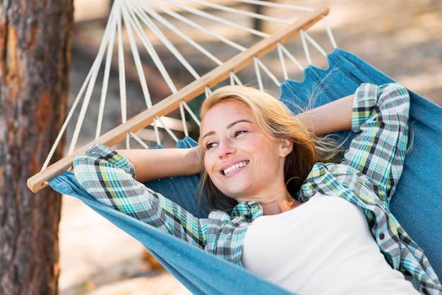 Vrouw zittend in een hangmat en wegkijken