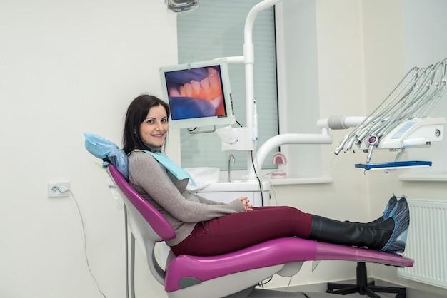 Vrouw zittend in tandartsstoel en wachtend op een dokter