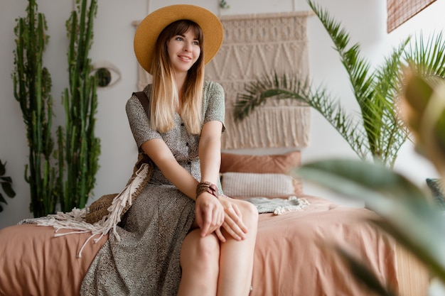Vrouw zittend op bed in haar boho appartement