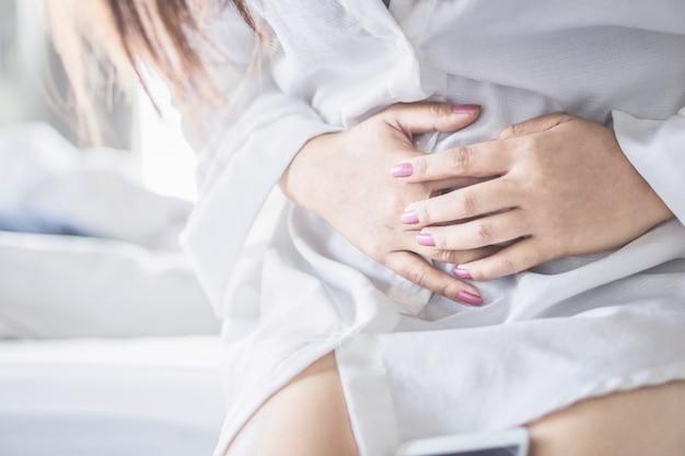 Vrouw, zittend op bed lijdt aan maagpijn