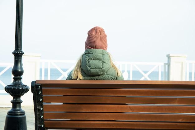 Vrouw zittend op de bank aan de kade met prachtig uitzicht op zee