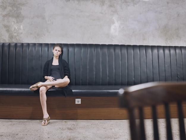 Vrouw zittend op de bank binnenshuis eenzaamheid wachten houten stoel op de voorgrond