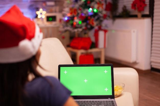 Vrouw zittend op de bank in een met kerst versierde keuken met een groen scherm mock-up chroma key laptop