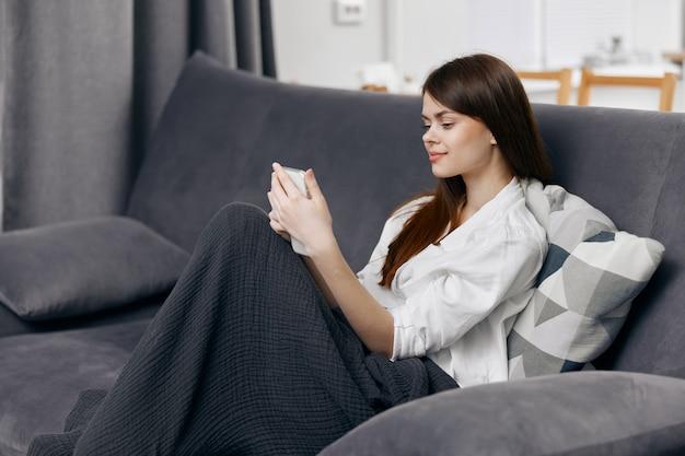 Vrouw zittend op de bank met een deken op haar schoot en een mobiele telefoon in haar hand.