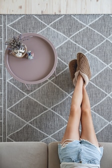 Vrouw zittend op de bank met haar voeten op het tapijt