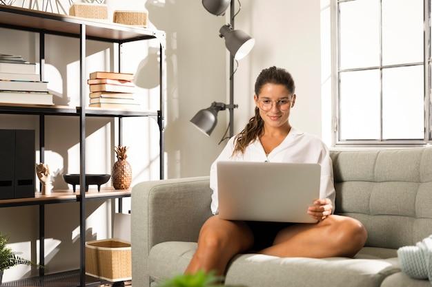Vrouw zittend op de bank met laptop