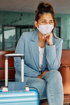 Vrouw zittend op de bank met medische masker en bagage op de luchthaven tijdens pandemie
