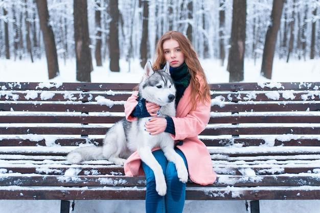 Vrouw zittend op de bank met siberische husky