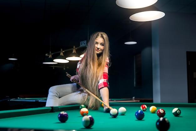 Vrouw zittend op de biljarttafel en gaand bal