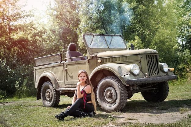 Vrouw zittend op de grond in de buurt van militaire auto