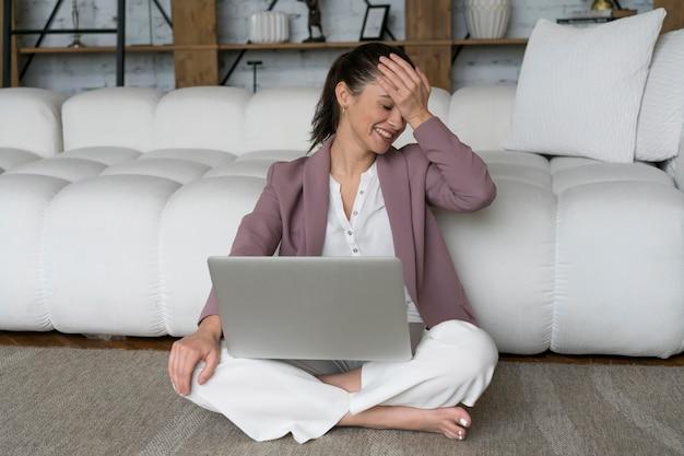 Vrouw zittend op de grond met een laptop op schoot