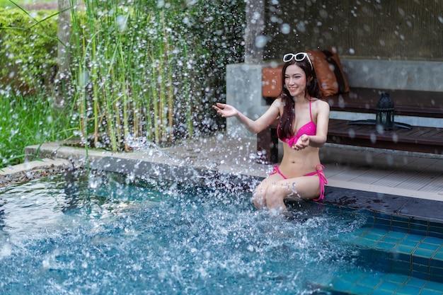 Vrouw, zittend op de rand van het zwembad en het spelen van water splash