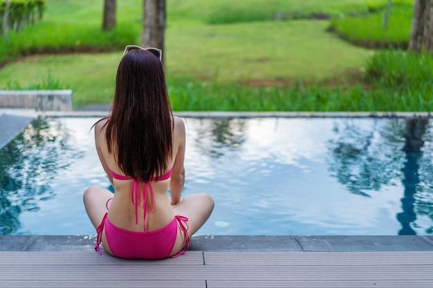 Vrouw, zittend op de rand van het zwembad