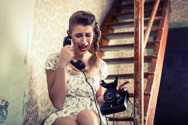 Vrouw zittend op de trap en huilen aan de telefoon