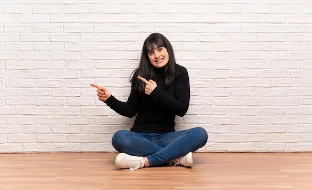Vrouw zittend op de vloer bang en wijzend naar de zijkant
