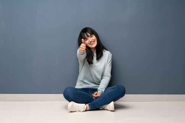 Vrouw zittend op de vloer handen schudden voor het sluiten van een goede deal