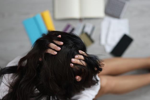 Vrouw zittend op de vloer in de buurt van verspreide bankkaarten en met haar hoofd bovenaanzicht economische crisis