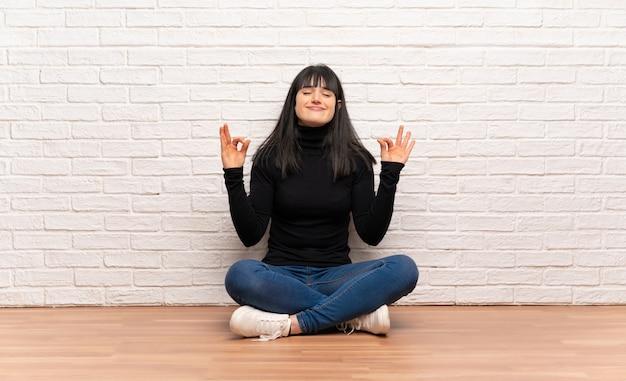 Vrouw zittend op de vloer in zen pose
