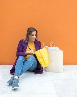 Vrouw zittend op de vloer kijken naar boodschappentassen