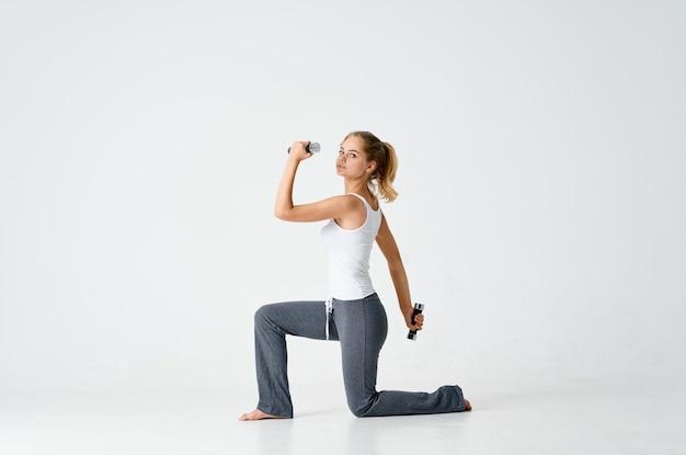 Vrouw zittend op de vloer met dumbbells workout oefening Premium Foto