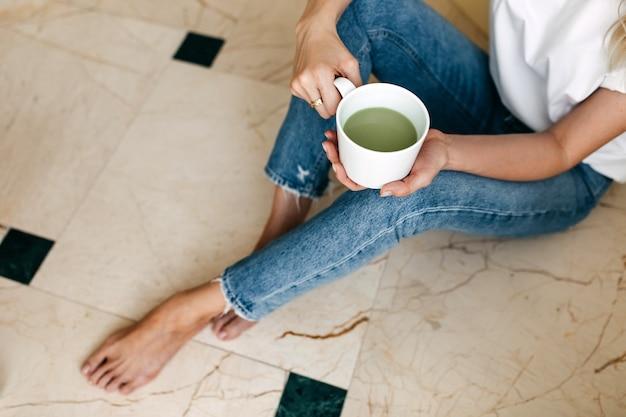 Vrouw zittend op de vloer met een kopje matcha latte