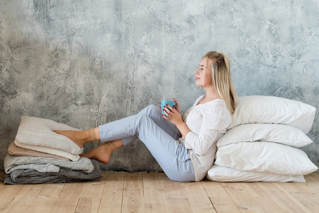 Vrouw zittend op de vloer met stapel kussens en gebreide dekens met kopje koffie. comfortabele vrije tijd thuis