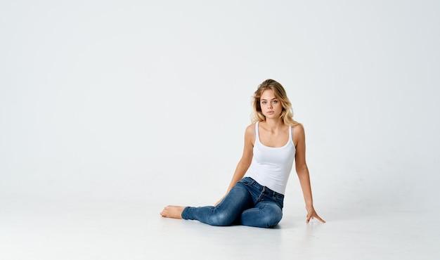 Vrouw zittend op de vloer poseren mode stijlvolle kapsel levensstijl